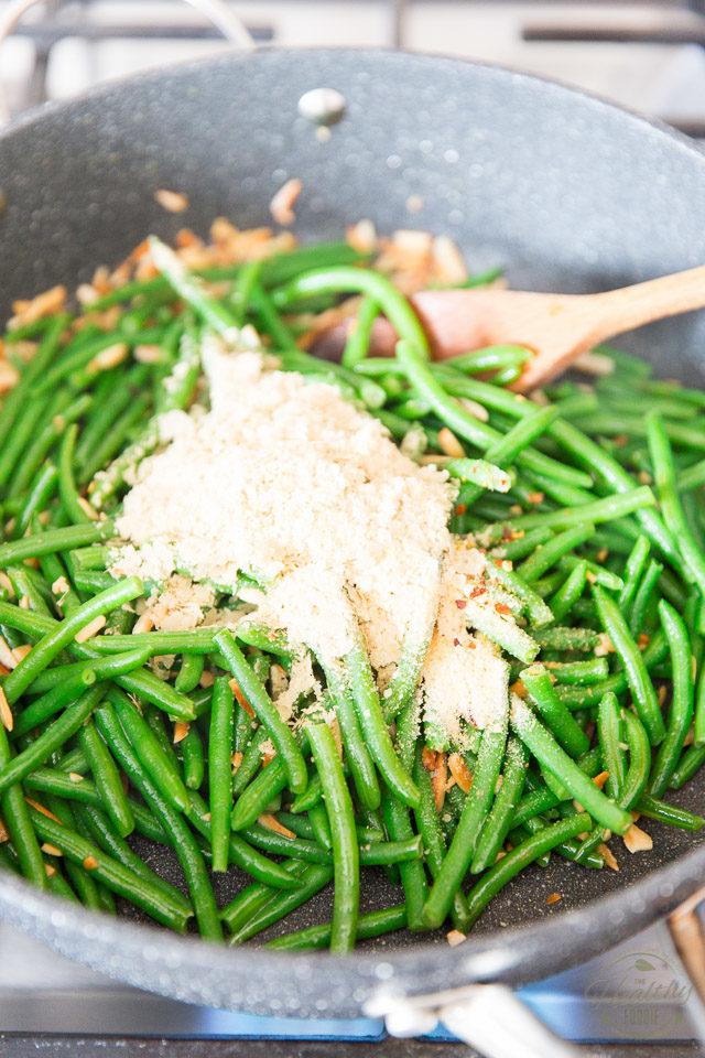 Add the nutritional yeast, red pepper flakes, onion powder, garlic powder and salt and stir well