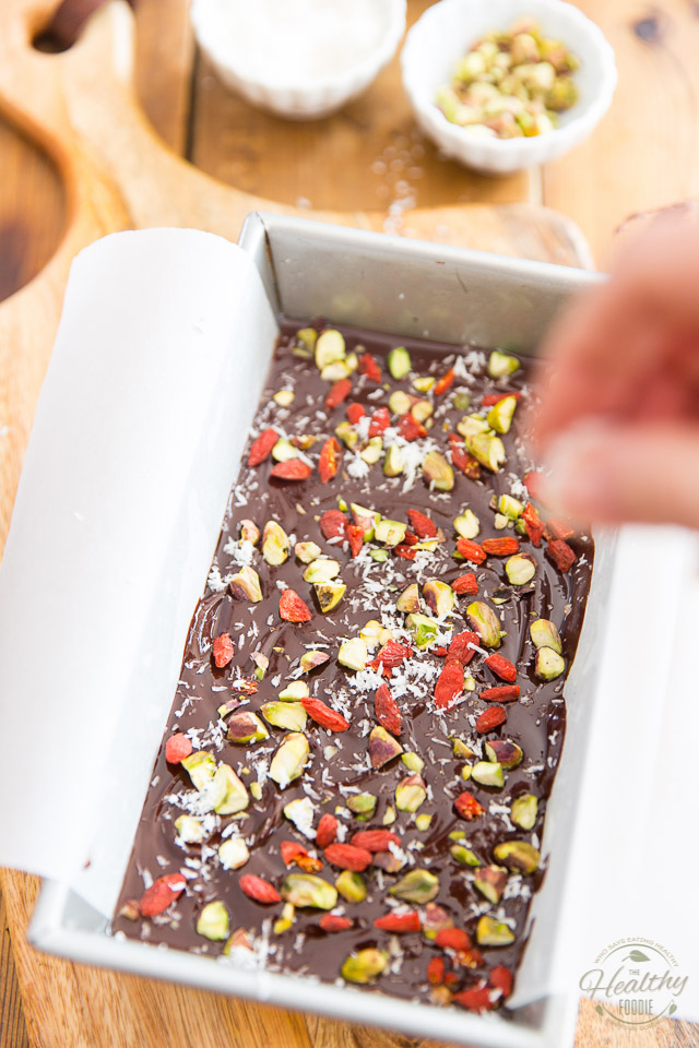 Garnishing the top of the fudge with goji berries, pistachios and coconut