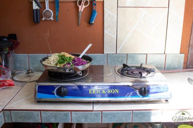 Dish ready to stir, sitting on rudimentary gaz stove top